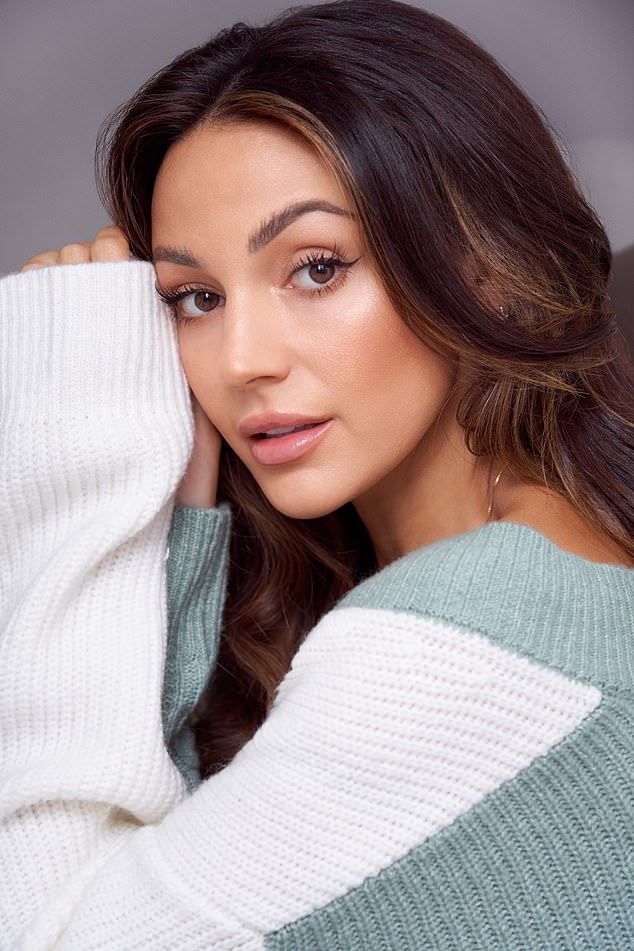 Cozy: For a look, she stayed warm in a white and blue knit sweater as she showed off her radiant complexion for the camera.