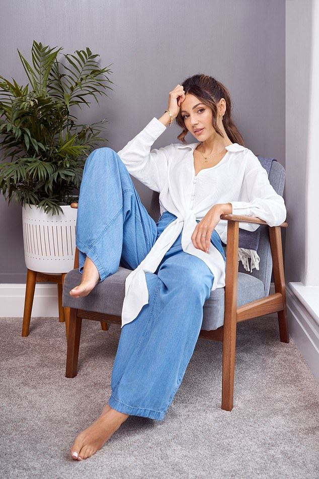 Cozy: Inside, the brunette beauty stretched out on a chair and donned a white shirt and wide-legged blue pants while staring at the camera with a stare