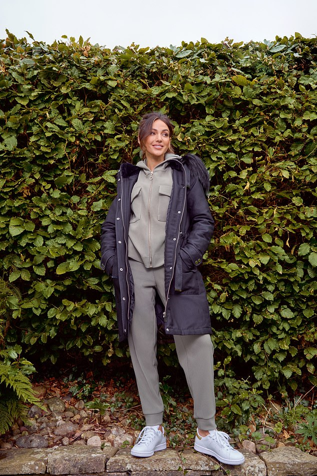 Casual: The collection also includes a khaki tracksuit that Michelle modeled under a black coat