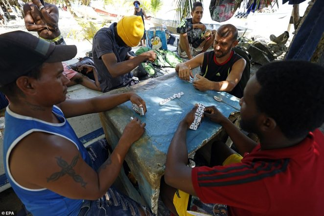 Haitian and Venezuelan migrants play dominoes in Necocli, Colombia on September 26 as theywait for space on the boats that will help them cross to the other side of the Gulf of Uraba
