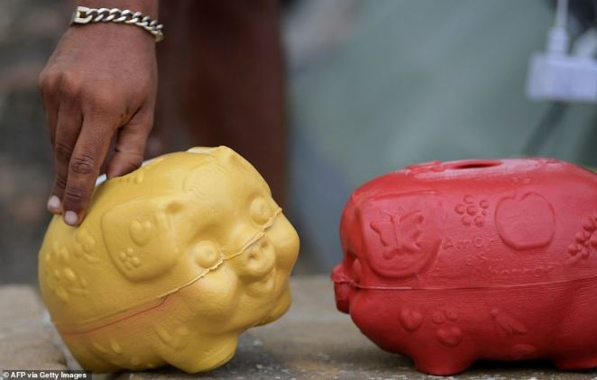 A migrant is seen touching a piggy bank in Necocli, Colombia over the weekend