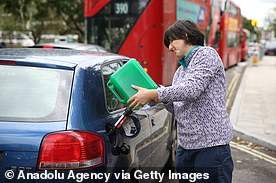 A motorist refuels his vehicle with a jerry can at a petrol station in London