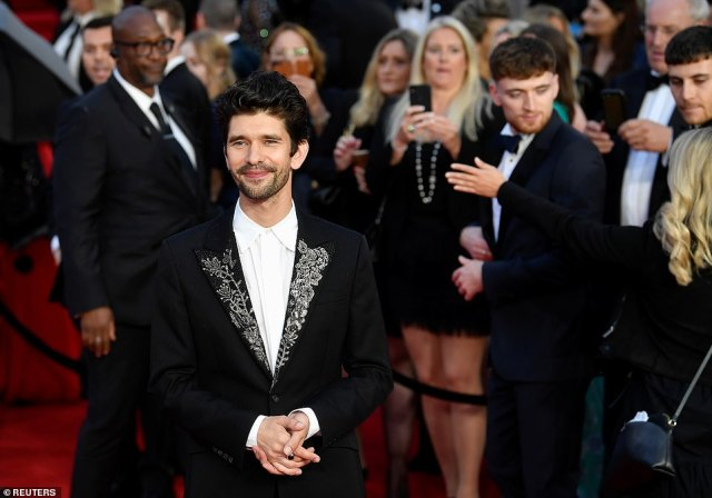 All in the details:Q actor Ben Whishaw opted for an embroidered suit jacket while posing for photographs on the red carpet