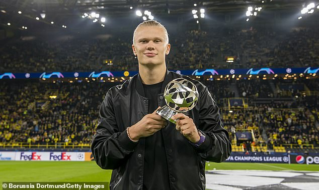 InjuredErling Haaland with the 2020/21 Champions League Forward of the Season trophy
