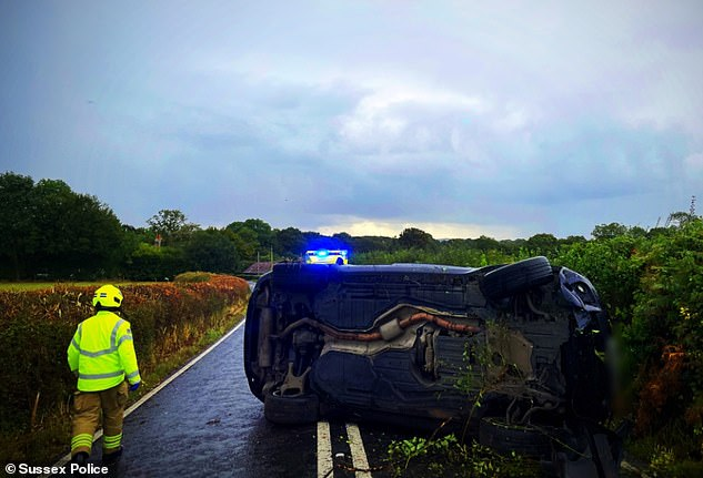 Evidence: A photograph tweeted by a police officer showed a damaged BMW lying on its side across both lanes of a country road near West Grinstead, its front lodged in the hedgerow following Katie's car crash