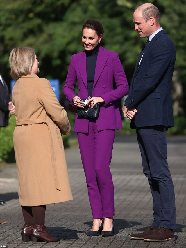 The Duchess of Cambridge, wearing a purple pantsuit, arrives for a visit to Magee University in Northern Ireland yesterday