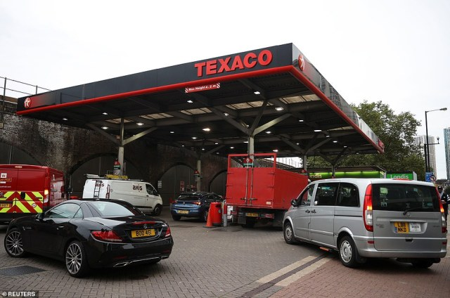 Vehicles queue to refill at a petrol station in London this morning amid the supply crisis