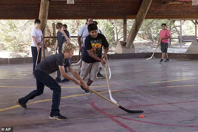 A new CDC report looked at 7,773 campers and staff at nine different overnight camps across the US between June and August 2021, and where 93% of those eligible were vaccinated.  Pictured: Campers play hockey at Broken Arrow Bible Ranch Camp near Vanderwagen, New Mexico, July 2021