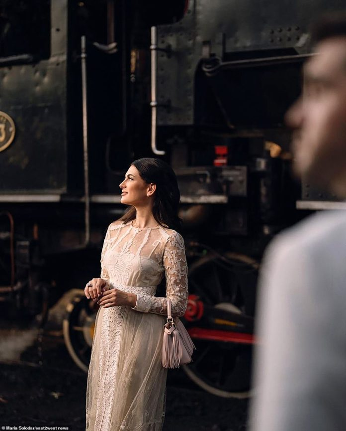 Picture perfect: The bride wore two dresses for the big day and posed in front of a train in her wedding photos