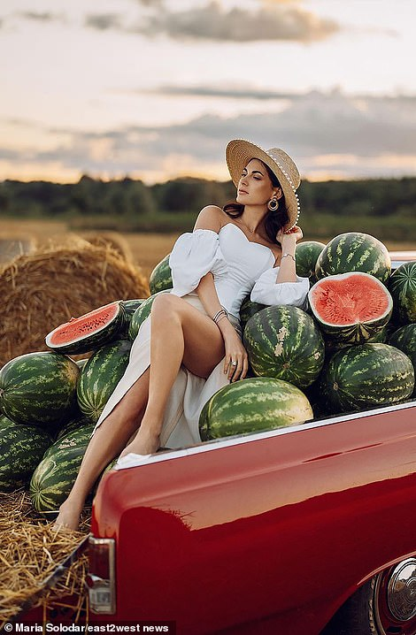 Taking full advantage of the wedding shoot, the bride poses on a bed of watermelon