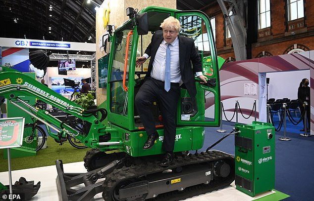 The PM poses with a digger during his party's annual conference in Manchester on Tuesday