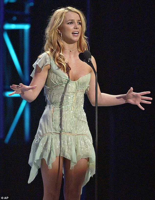 Reference: In the song she asks 'Who am I if not exploited' while rocking the same Robert Cavalli dress Spears stunned in at the 2003 American Music Awards, above