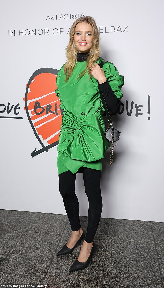 Looking good:Fellow model Natalia Vodianova cut a trendy figure in a green mini dress with a wrap detail which she wore with black tights
