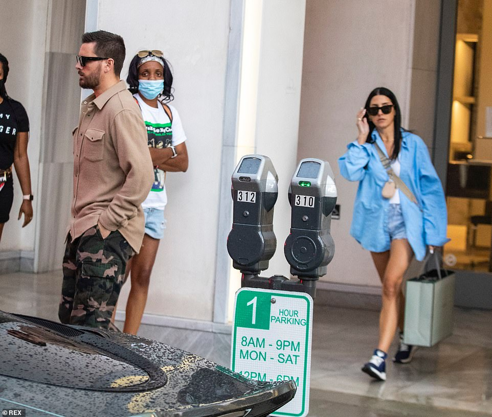 Making their way: After they were done at Tom Ford, the assistant followed Scott outside carrying a shopping bag