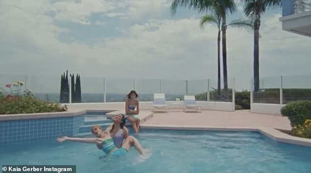 Doesn't fit in: The model watches her friends splash around in the pool without her