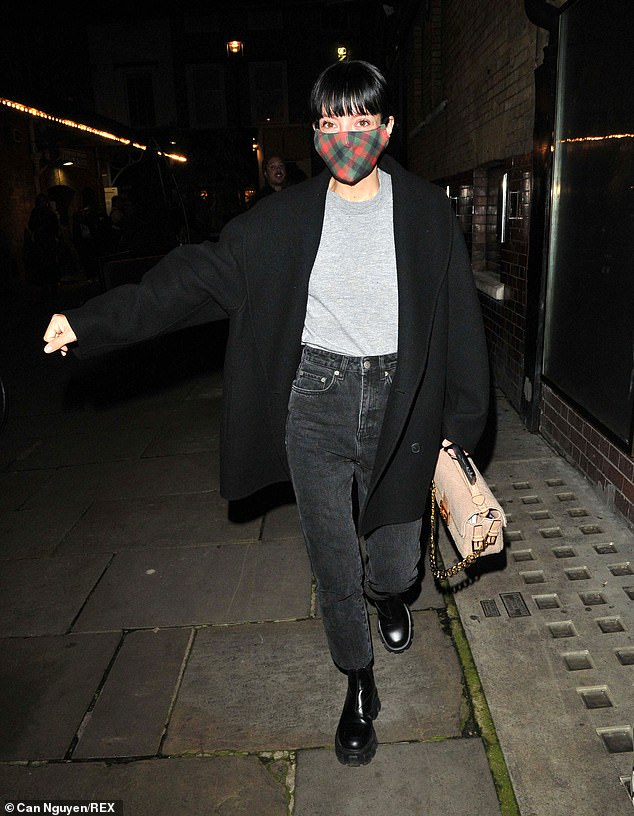 Stunning: Lily saved herself from coronavirus as she wore a red, green and black checkered mask while carrying her belongings in a cream Fendi handbag.