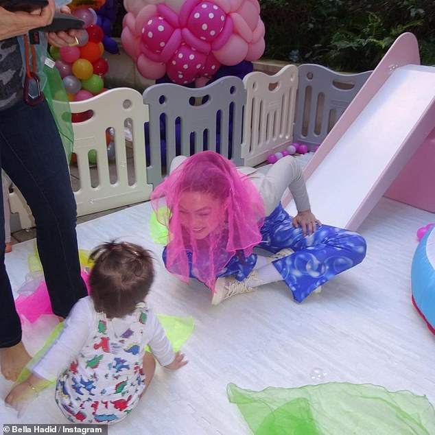 That's her girl! The model beamed with joy playing with her daughter with a pink veil over her face