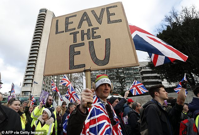 Protesters hold up placards and Union flags as they attend a pro-Brexit demonstration promoted by UKIP in central London in 2018