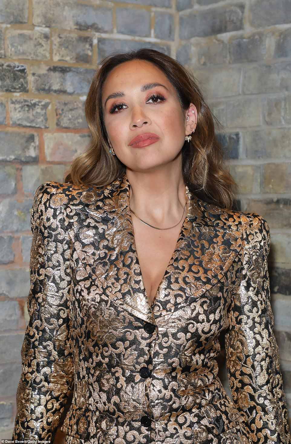 Radiant:Myleene wore a black and gold suit as she posed for the cameras at the event, accessorising with a black bag and slick of pink lip for her makeup