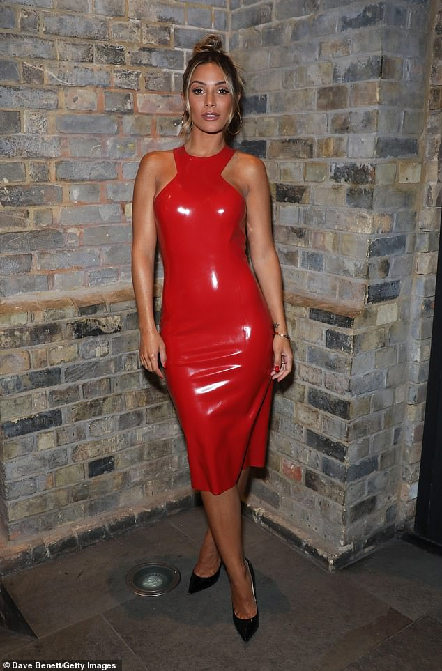 Pose: The Loose Woman star, 32, flaunted her stunning figure in a red PVC midi dress that featured a halterneck design and was teamed with pointy black heels.