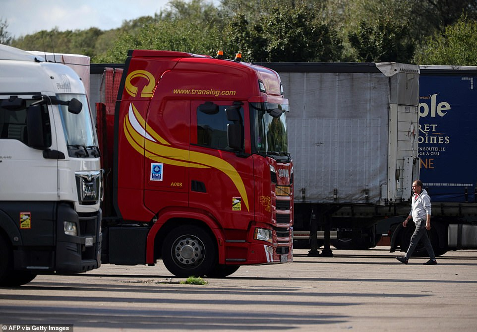 A driver walks between the lorries at Ashford International truck stop, in Ashford, south-east England on October 5, 2021