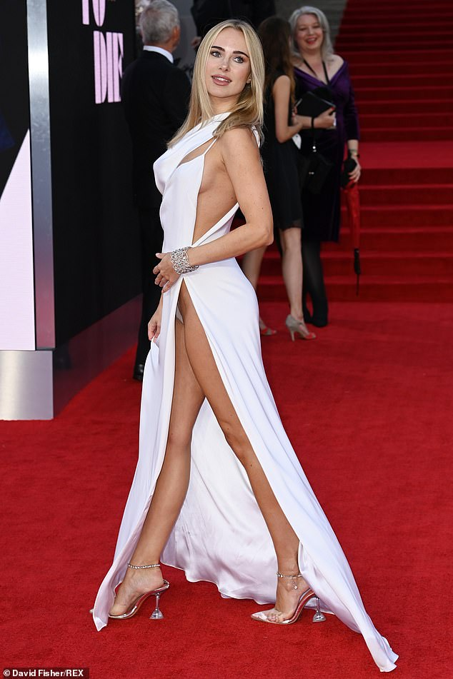 Kimberly Garner, 30, made an absolutely stunning appearance on the red carpet for the star-studded screening of No Time to Die in London last week in a daring white cut-out gown.