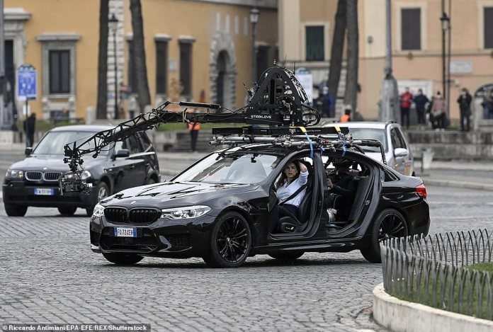 Tom Cruise with actress Hayley Atwell in a car during filming at Rome's Piazza Venezia