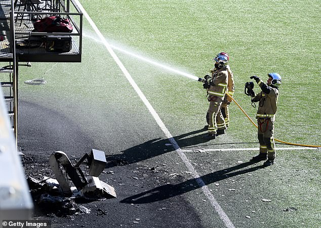 Emergency services are shown putting out the fire on the side of the pitch above the dugout