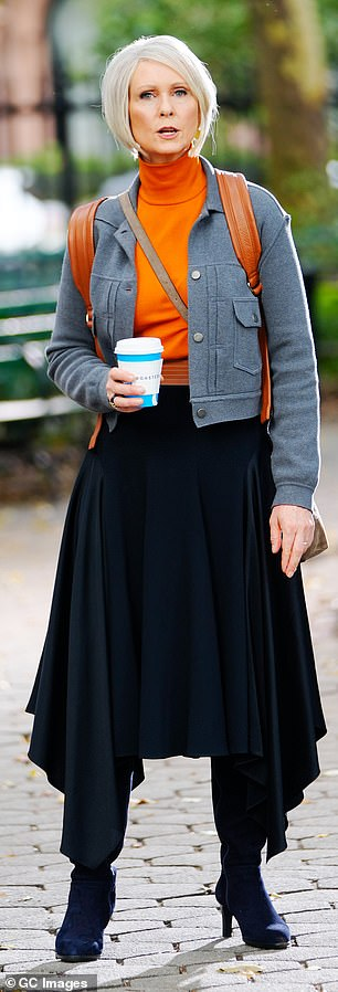 Autumn style: The seasoned entertainer dazzled in an orange turtleneck, grey jacket, and a long black skirt, black boots