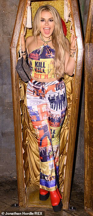 Blindfold: Talia Storm, who sought attention in a mismatched Kill Bill-inspired multi-colored jumpsuit, soon took her turn to pose inside the prop