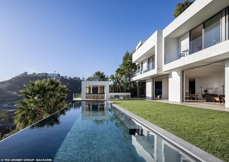 The outlet told readers: 'From inside the gated motor court, the front of the sleek home looks like three simple white and grey cubes, and that same expressive simplicity continues into the interior'