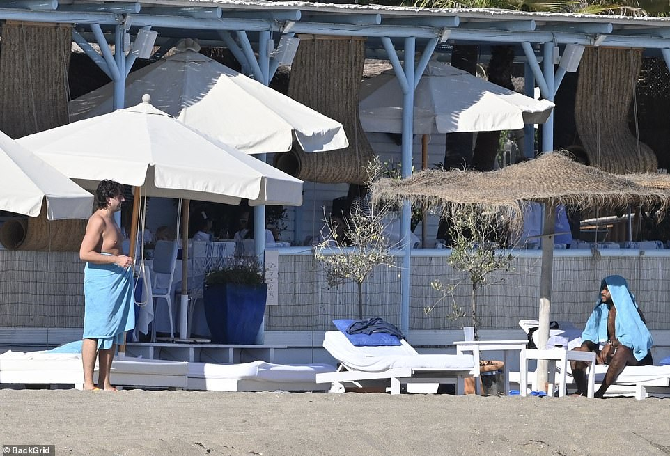 Having fun in the sun: He wrapped a blue towel around his waist after the sunbathing session