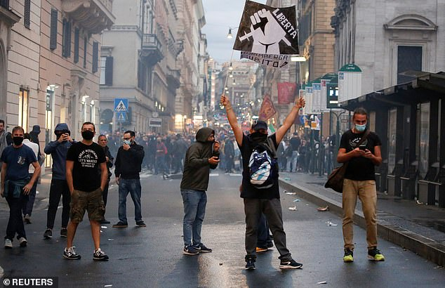 This summer, Green Passes were required in Italy (pictured: protest in Rome) to enter museums, theatres, gyms and indoor restaurants, and take long-distance trains and buses