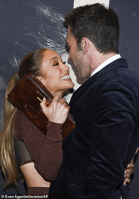 Privacy please! As they puckered up, a shy looking Jennifer beamed at her rekindled flame and attempted to shield their affection with her clutch