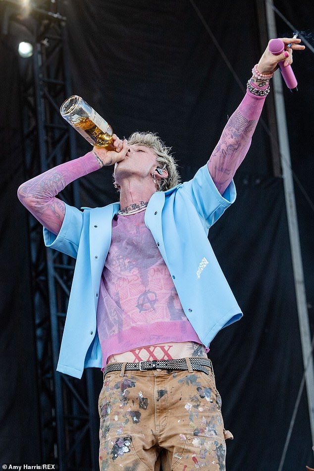 Bottoms up: MGK heavily leaned into his newfound 'rocker' persona by chugging a bottle of alcohol on stage during his energetic set
