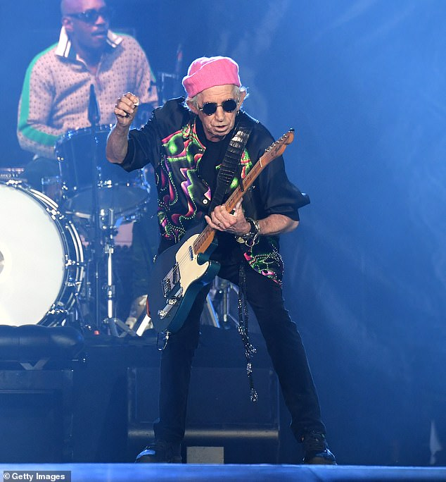 Born to perform:Keith sported a pink beanie on his head while he wore a multi-coloured patterned top as he played his baby blue and white guitar