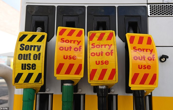 Signs reading 'Sorry out of use' are displayed on the pumps of a closed petrol station in London