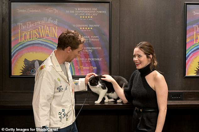 Furry friend: The actors beamed for the camera as they embraced and stroked a cat for a few snaps
