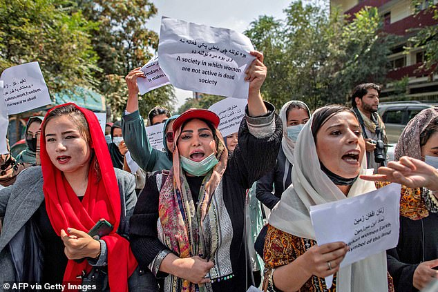 Afghan women hold placards during a demonstration demanding better rights for women in front of the former Ministry of Women Affairs in Kabul on September 19, 2021