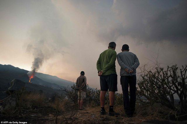 People observe as the Cumbre Vieja volcano spews lava, ash and smoke, in Los Llanos de Aridane, on Sunday