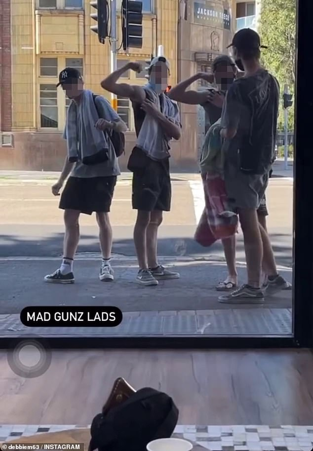 The video shared online shows the group appearing to be unaware there is actually a shop full of people on the other side of the window (pictured)