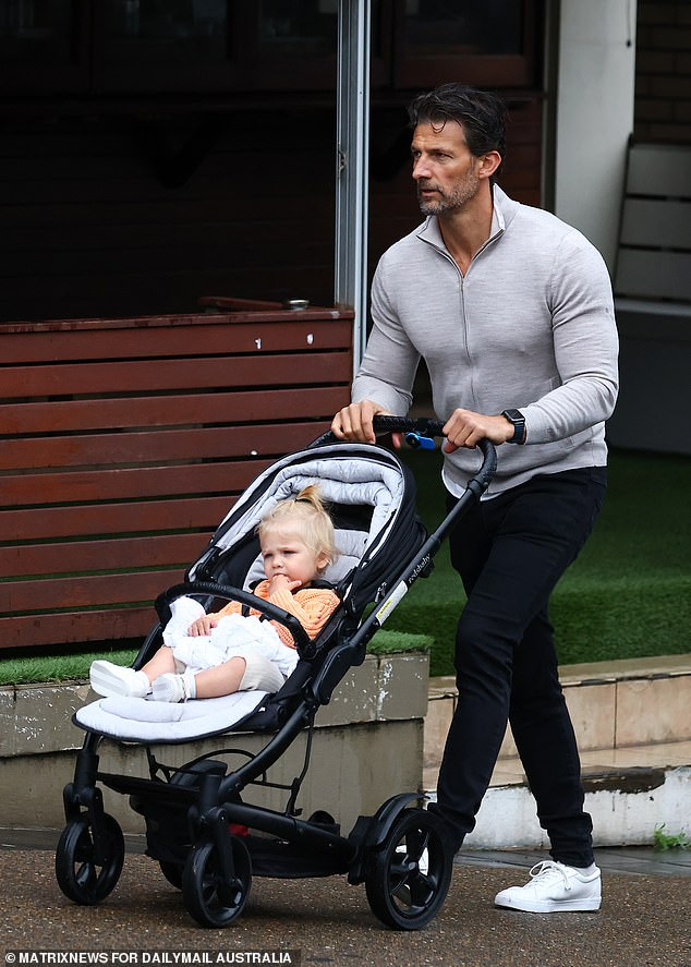 Feeling nippy, Tim? Robards, 39,(pictured) showed off his bulging pecs in a skintight grey top as he steps out for breakfast at swanky Bills in chilly Sydney with daughter Elle on Monday