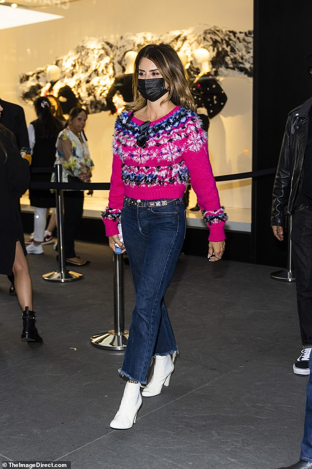 Bright:On her top half she donned a bright pink sweater that was accented with a 3D blue, white, and black pattern on the cuffs of her sleeves and along the front