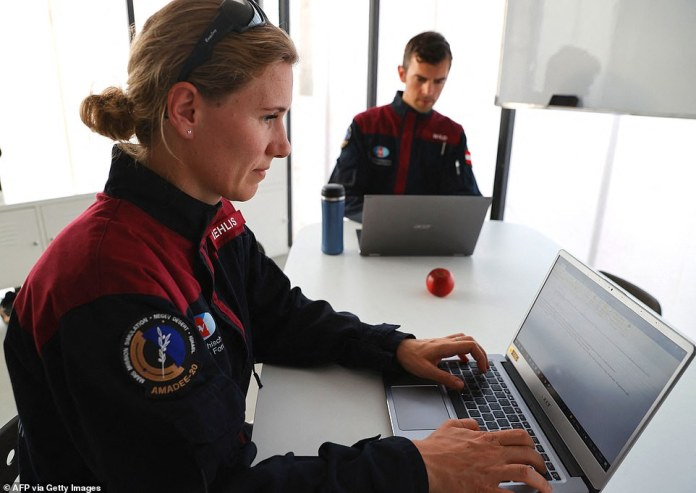 German astronaut Anika Mehlis and Austrian colleague Robert Wilde use laptop computers before the mission