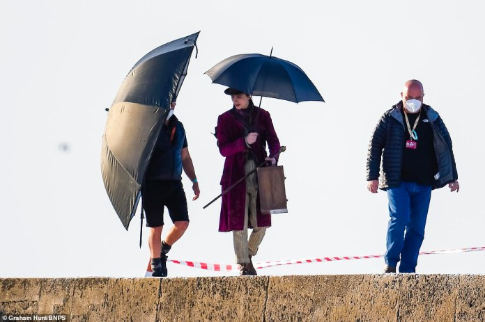 Filming:Timothee also sported a pair of gold striped trousers and carried a large brown suitcase as he was joined by two crew members for the shoot