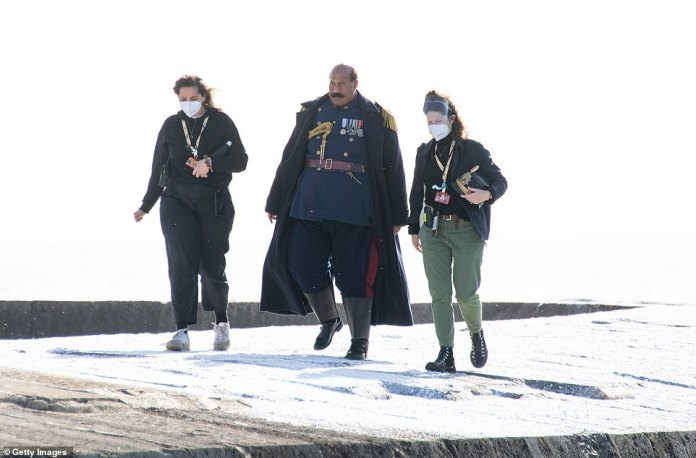 In character: Tom Davis wrapped up in a black coat as he was joined by two crew members during filming