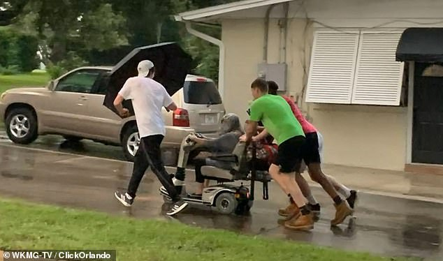 Touching photos captured the moment four young men pushed an elderly woman down a Florida neighborhood after her scooter broke down in the middle of a storm