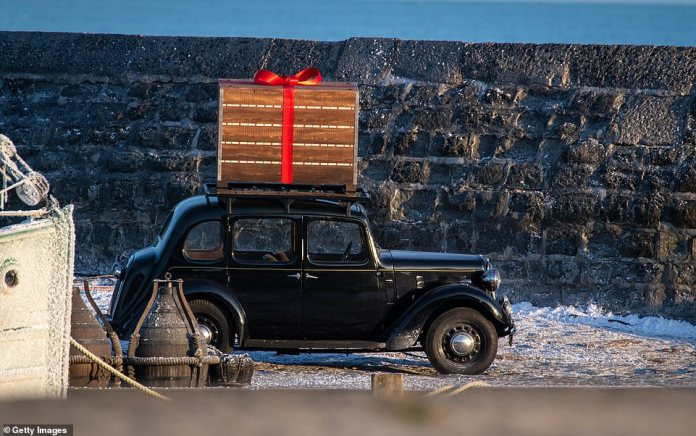What's that?A vintage car with a large wrapped gift on the roof travelled onto set