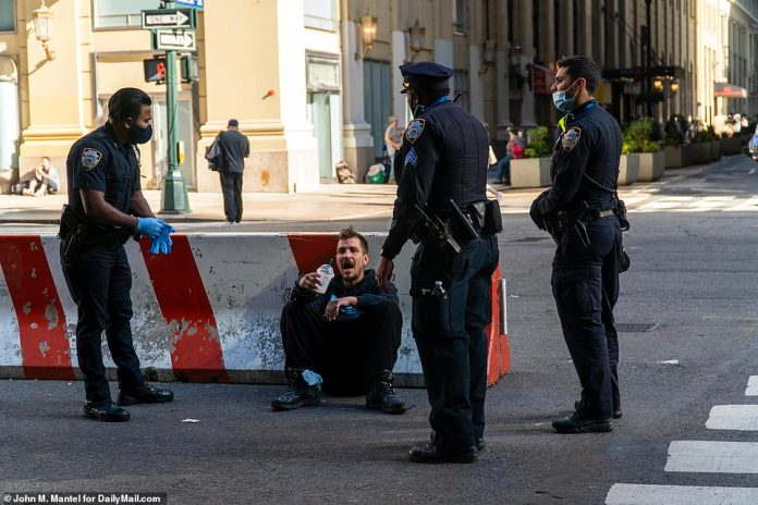 A homeless man is pictured talking to cops while sat against a concrete barrier next to Penn Station in Midtown Manhattan