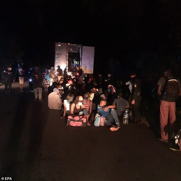 Migrants wait for assistance on the side of a road in southern Guatemala on Saturday after they were rescued from a locked truck abandoned by smugglers they had contracted to ferry them to Mexico and the United States
